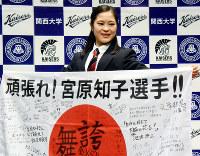 学校関係者の激励メッセージが書かれた日の丸を手に笑顔を見せる宮原=大阪府吹田市の関大で2018年1月18日、浅妻博之撮影