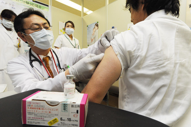 インフルエンザワクチンの接種を受ける男性=東京都内の国立病院で2010年2月10日、代表撮影