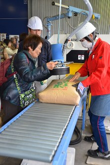 A woman, left foreground, participates in a tour to experience the blanket screening of Fukushima-produced rice for any radioactive materials. (Mainichi)