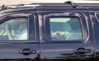 ゴルフ場からの帰りの移動中、車の後部座席に座って携帯電話を操作するトランプ米大統領=米南部フロリダ州パームビーチで2017年2月、AP