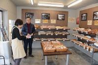 開店準備をする野崎さん(右)。店内にはかつての下本町商店街の写真が飾られている=新潟市中央区で