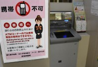ATMコーナーで携帯電話が使えないことを知らせる張り紙。携帯電話で実際に発信しようとすると、通話がすぐに終了したり、「発信できませんでした」のメッセージが画面に出たりする=伊勢崎市役所で