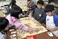 社会科の授業中に「季節のうつろい たべものすごろく」で遊ぶ子どもたち=東京都練馬区の光が丘秋の陽小で16日、銅山智子撮影(画像の一部を加工しています)