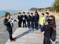 高知県立山田高の生徒らにドローンの扱い方を説明するマイクロソフト業務執行役員の西脇資哲さん(左)=高知県香南市夜須町千切の「ヤシィパーク」の海岸で、村瀬達男撮影