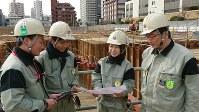 土壌の浄化対策について現場の所長らと話し合う仁井直子さん(右から2人目)=東京都豊島区で