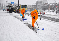 City workers shovel snow that has accumulated on a sidewalk in front of municipal government headquarters in Machida, western Tokyo, on Jan. 22, 2018. (Mainichi)