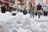 雪が残る歩道を歩く人たち=東京都渋谷区で2018年1月23日午前10時25分、藤井達也撮影