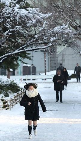 歩道に雪が残る中、目的地に向かう人たち=東京都千代田区で2018年1月23日午前7時29分、佐々木順一撮影