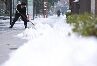 朝から歩道で雪かきをする人=東京都千代田区で2018年1月23日午前7時20分、佐々木順一撮影