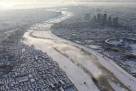 雪化粧した多摩川の河川敷。川面からは湯気が立ち上っていた=東京都世田谷区で2018年1月23日午前7時38分、本社ヘリから