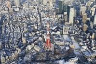 雪に覆われた東京タワー周辺の街並み=東京都港区で2018年1月23日午前7時43分、本社ヘリから