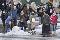 道路脇に寄せられた雪で遊ぶ子どもたち=東京都渋谷区で2018年1月23日午前9時50分、藤井達也撮影
