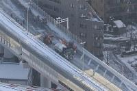 大雪の影響で通行止めとなった首都高7号線で行われた除雪作業=東京都墨田区で2018年1月23日午前7時58分、本社ヘリから
