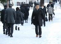 歩道に雪が残る中、職場などに向かう人たち=東京都千代田区で2018年1月23日午前8時17分、佐々木順一撮影
