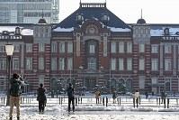 雪が残る東京駅を撮影する人たち=東京都千代田区で2018年1月23日午前10時8分、佐々木順一撮影