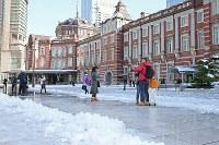 雪が残る東京駅で記念撮影する人たち=東京都千代田区で2018年1月23日午前10時18分、佐々木順一撮影