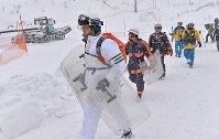 Police officers walk toward the summit of Mount Kusatsu-Shirane to conduct a search at Kusatsu Kokusai Ski Resort in the town of Kusatsu, Gunma Prefecture, on Jan. 24, 2018. (Mainichi)