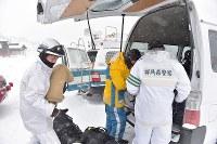 山頂付近の捜索が中止となり車に荷物を積み込む警察官たち=群馬県草津町の草津国際スキー場で2018年1月24日午後0時51分、藤井達也撮影
