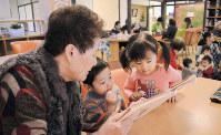子供たちに絵本を読み聞かせするデイサービスセンター「梅本の里・小梅」の利用者(左端)=松山市で