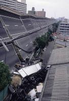 横倒しになった高速道路。トラックが重なるように転がり、車体の底を見せていた=神戸市東灘区で1995年1月17日、長島義明さん撮影