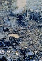 地震発生から3日目になるというのに、まだ燃え続ける神戸・長田地区。空から見ると、その焼けた広さに驚く=1995年1月19日、長島義明さん撮影