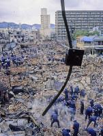 焼け落ちた街には、がれきの下に多くの被災した死者が埋もれていた。自衛隊や警察の機動隊員らが懸命に発掘作業を続け、韓国からも捜索に隊員が参加した=神戸市長田区の菅原市場周辺で1995年1月20日過ぎ、長島義明さん撮影