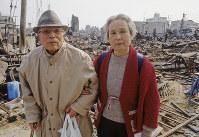 「戦災後、こんな恐ろしい目にあったのは初めて」と語った老夫妻。背後には戦争後のような焼け跡が広がっていた=神戸市長田区で1995年1月20日過ぎ、長島義明さん撮影