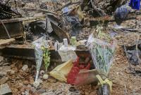 ぽつんと置かれた花束やコーヒー、お茶、お酒、おにぎりなどは遺族のねぎらいであろう。焼け跡の中でそれが一番悲しさをさそった=神戸市長田区で1995年1月20日過ぎ、長島義明さん撮影