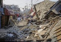 倒壊した家々の中、布団を運ぶ被災者=神戸市長田区で1995年1月20日過ぎ、長島義明さん撮影