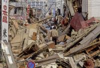 家々が倒壊した中をゆく被災者=神戸市長田区で1995年1月20日過ぎ、長島義明さん撮影