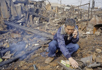 「何もかも燃えてしもうたんや。この先どうなるかわからへん」。男性がまだくすぶる焼け跡で仕事先へと電話をしていた=神戸市長田区で1995年1月20日過ぎ、長島義明さん撮影