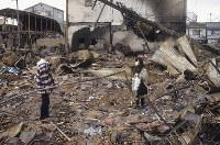 「・・・・・」。焼け跡に立つ被災者の家族。靴音さえ拒まれるような時間だった=神戸市長田区で1995年1月20日過ぎ、長島義明さん撮影