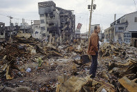焼け跡にぼうぜんと立つ男性=神戸市長田区で1995年1月20日過ぎ、長島義明さん撮影