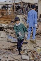 思い出を探しているのだろうか。焼け跡で何かを探す子ども=神戸市長田区で1995年1月20日過ぎ、長島義明さん撮影