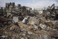 焼け跡で何かを探す被災者=神戸市長田区で1995年1月20日過ぎ、長島義明さん撮影