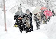 雪が降る中、金沢大のセンター試験会場に向かう受験生たち=金沢市で2018年1月13日