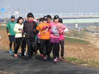 1キロ7分45秒のペースメーカーになった宮崎亜希さん(手前)の先導で走る参加者ら=久喜市で21日
