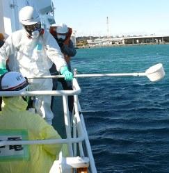 巡視船「ふじ」の甲板上で測定用の海水を採取する訓練参加者ら=御前崎市の御前崎港で