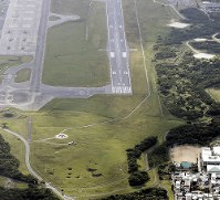 Futenma No. 2 Elementary School, foreground right, and the U.S. Marine Corps Air Station Futenma are pictured in Ginowan, Okinawa Prefecture, in this photo taken from a Mainichi aircraft on Dec. 13, 2017. (Mainichi)