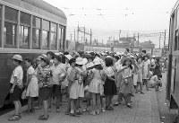 都民の足、都電の数路線が新宿駅に集まっていた。靖国通りにある停留所で、水筒を肩に遠足のための貸し切り電車を待つ小学生たち=東京都新宿区で1955年、写真家の中谷吉隆さん撮影