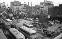 新宿駅東口駅前。地下鉄丸ノ内線の新宿への延長工事で新宿通り(手前)は渋滞。池袋~新宿間は1959年に開通した。右端に駅舎が見える=東京都新宿区で1957年、写真家の中谷吉隆さん撮影
