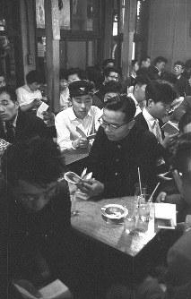 新宿は若者、学生の町でもある。うたごえ喫茶や酒場ではアコーディオンの伴奏で、客は小さな歌詞本を片手にロシア民謡などを歌い、連日連夜満員だった=東京都新宿区で1958年、写真家の中谷吉隆さん撮影