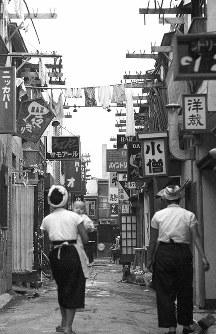 狭い間口のバ―や飲み屋が密集する花園町。1958年の売春防止法の完全施行で廃業するまで、青線と呼ばれる風俗営業の地で、物干しにはおしめなど生活の匂いがぷんぷんとしていた=東京都新宿区で1958年、写真家の中谷吉隆さん撮影