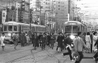 靖国通りにある停留所で降り、旧国鉄の駅に向かう会社員ら=東京都新宿区で1965年、写真家の中谷吉隆さん撮影