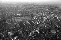 新宿駅の西側。中央は都民に67年間、生活用水を供給し続けてきた旧淀橋浄水場。中央右側が新宿駅、下部に当時モダンな建物だった文化服装学院の円筒形のビルが見える。左手前が新宿ガスタンク=東京都新宿区で1965年、写真家の中谷吉隆さん撮影