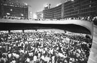 ベトナム戦争が激化する時期に西口地下広場で行われた反戦フォークソングの集会。タクシー乗り場まで群衆で埋まった。このあと群衆は警察官に排除された=東京都新宿区で1969年、写真家の中谷吉隆さん撮影