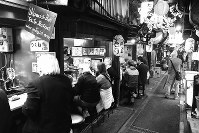 「思い出横丁」には、マッチ箱のような大衆食堂やヤキトリ屋が一時は約300軒もあった。「ハモニカ横丁」「ションベン横丁」とも言われた。学生時代によく通った「つるかめ」は今も健在。昭和の雰囲気が残る地として、外国人が多く訪れ英語の看板も出現した=東京都新宿区で2017年、写真家の中谷吉隆さん撮影