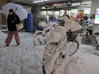 コンビニの前に置いてあった自転車もあっという間に雪に覆われた=東京都立川市で2018年1月22日、小林努撮影