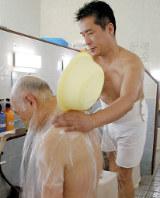 入浴客の背中を流す右田智弘さん(右)=神奈川県座間市で