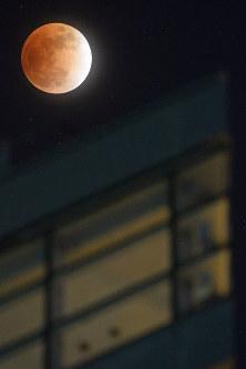地球の影に覆われ、赤銅色になった月。下は大洗マリンタワー=茨城県大洗町で2018年1月31日午後10時11分、渡部直樹撮影